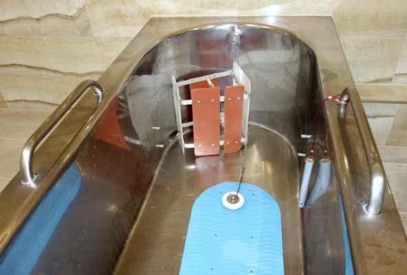 """V každé vaně je protiskluzová podložka, stolička, o kterou se zapřou nohy a kdo je hodně malý dá se vana """"zkrátit"""" přepážkou - ta se dává mezi ty kolíčky na stranách. Pak je tu teploměr - koupel má mít na začátku 36 - 37°, víc ne. A ještě je možné dostat pod hlavu nafukovací """"polštářek"""". Radonová voda do vany přitéká otvorem dole  vlevo."""
